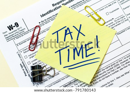A W9 tax form with tax time written on a sticky note.