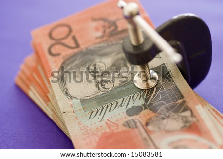 a wad of australian 20 dollar notes pressed in a G clamp