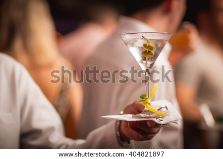 A waiter holding a dry martini in a classic glass