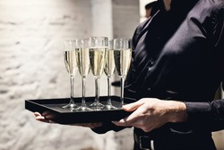 A waiter holding glasses with champagne served on a tablet