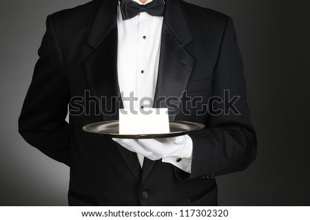 A waiter or butler wearing a tuxedo holding a note card on a silver tray in front of his torso. Man is unrecognizable over a light to dark gray background.