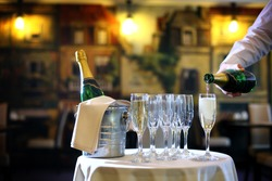a waiter pouring champagne in the glasses in the restaurant