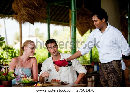 A waiter pours wine for a couple having dinner at a resort restaurant on vacation