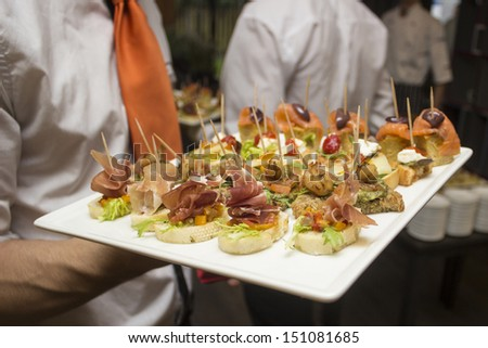 a waiter serving appetizers during a catered event