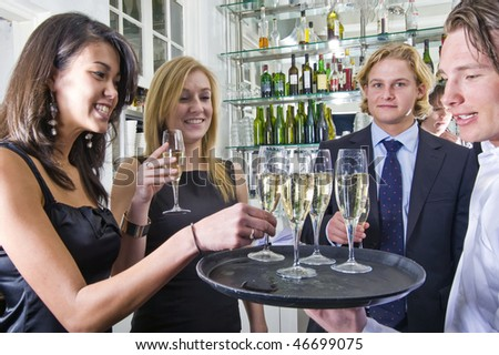 a waiter serving glasses of champagne on a tray in a restaurant