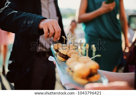 A waiter with a tray of snacks at a banquet or reception. Catering buffet at party #1043796421