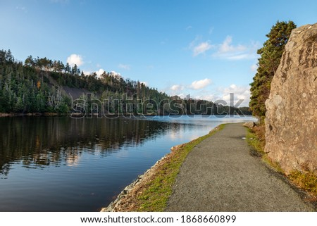 A walking trail of crushed stone and gravel along a wide river. The trail has water on one side and a rock face cliff on the other side. The stream is calm and reflecting the mountain covered in trees Stockfoto ©