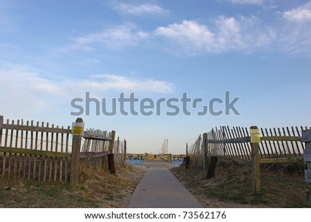 A walkway down the sidewalk through the Beach on the way to the fishing pier with a bright blue sky and room for your text. #73562176