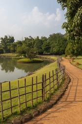 A walkway in a park with fence and pond in one side and trees and siting bench on the other
