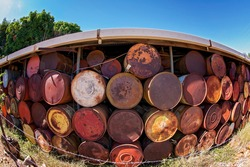 A wall made from rusted drums photographed with a fisheye lens
