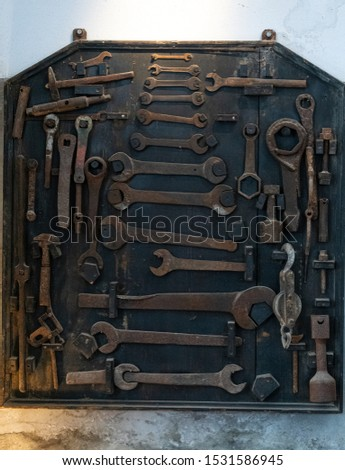 A wall mounted selection of old spanners, wrenches and other tools. #1531586945