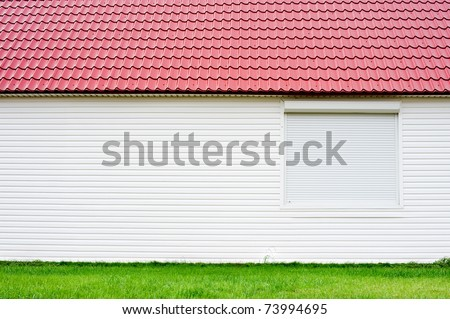 a wall of a white house with a red roof on green grass