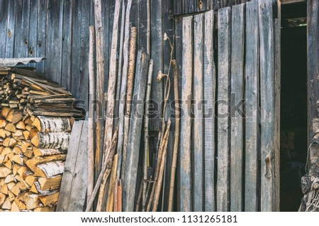 A wall of an old wooden shed. Birch firewood, boards and trees stacked next to him. Doors open. Vintage. #1131265181