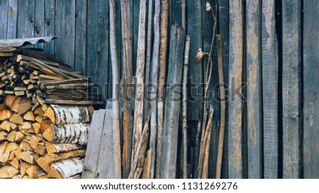 A wall of an old wooden shed. Birch firewood, boards and trees stacked next to him. Vintage #1131269276