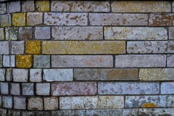 A wall of rubble stone. Various natural shades of stone: yellowish, grayish, pinkish. Background for design.
