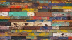 A wall of worn colored timber boards