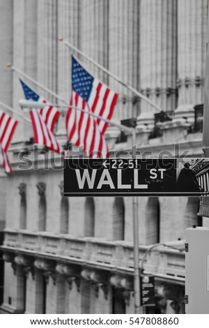 A wall street sign in front of the American flags #547808860