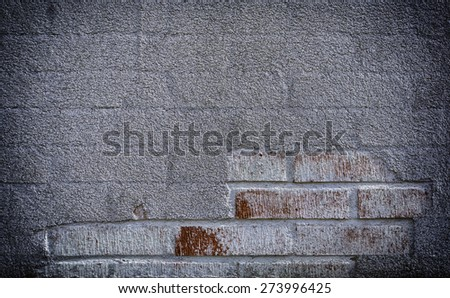A wall with damaged plaster followed by brick.  Brick wall