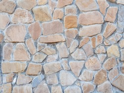 A wall with disorderly stonework. Background texture. Full screen