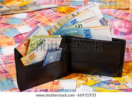 A Wallet with Swiss Francs in it, standing on a Floor with other Swiss Francs Banknotes