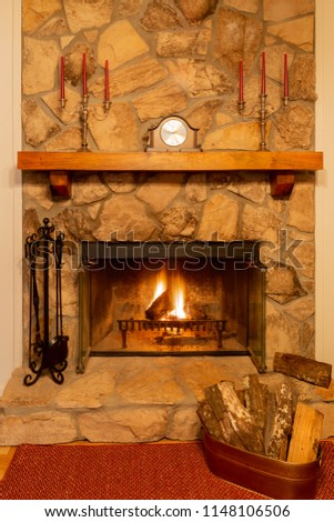 A warm fire in a beautiful stone fireplace with clock and candelabras on the mantle.