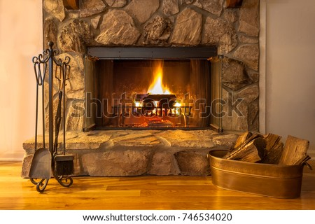 A warm fire in the stone fireplace on a cold night #746534020