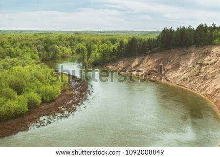 A warm spring day in the forest valley of the Russian river with a steep sandy slope. Landscape #1092008849