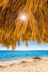 A warm summer day on holiday near the sea: large straw umbrella on an empty sandy beach, providing pleasant shade