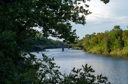 A warm sunny day provided a beautiful scenic photograph of a bridge over waters in a Kansas river with lots of green trees.