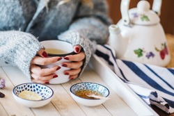 a warm tea to heat a cold winter. The girl is holding herbal tea. a cup of linden tea