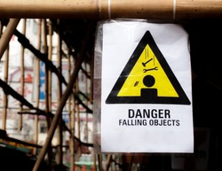 A warning sign hanging on a pole at a construction site. The words