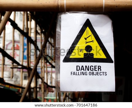 """A warning sign hanging on a pole at a construction site. The words """"Danger Falling Objects"""" are written on it."""