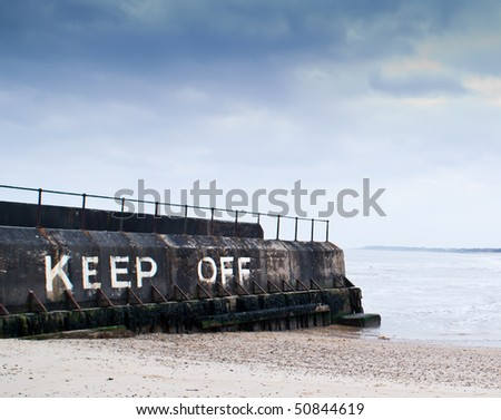 "A warning sign ""Keep Off"" written on jetty on the seaside"