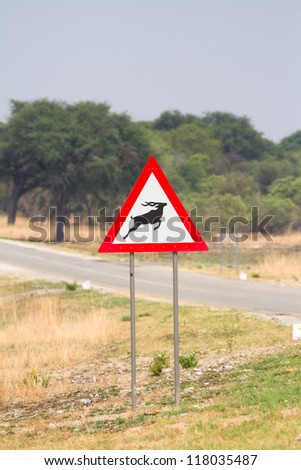 A warning sign with a picture of a jumping kudu bull on it
