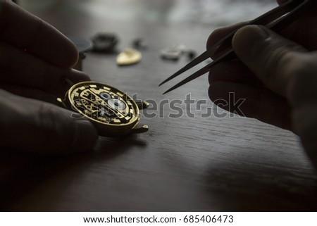a watch maker is repairing a...