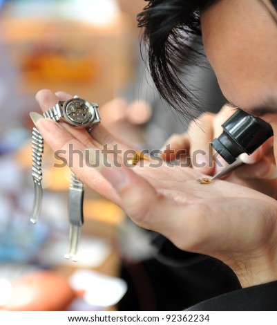 A watchmaker or repair man in action, viewing very closely a watch.