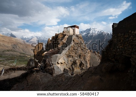 A watchtower at the old mountain monastery in Dhankar is set against a stunning Himalayan mountain range backdrop in the Spiti Valley in Himachal Pradesh state of northern India. Horizontal copy space