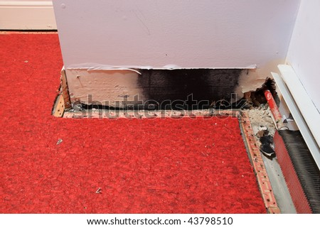 a water damaged wall from leaking pipe with carpet pulled back to dry