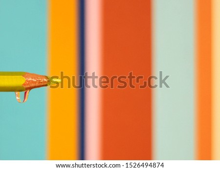 A water drop on the top of the colored pencil on colorful stripes background