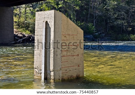 A water gage on two sides of a concrete block in a river.  Used by kayaks and rafters.