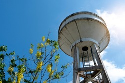 A water tank made of cement under the blue sky and has trees adorning the side.