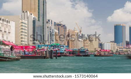 A water taxi boat station in Deira timelapse. Cloudy sky and skyscrapers on background, Here, passengers can board a Dubai Water Taxi to travel around the emirate on certain set routes.
