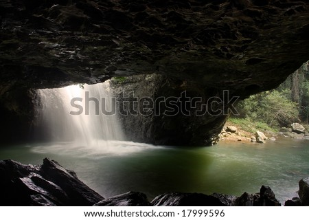 a waterfall breaks through the roof of a dark cave in Springbrook National Park, Queensland, Australia
