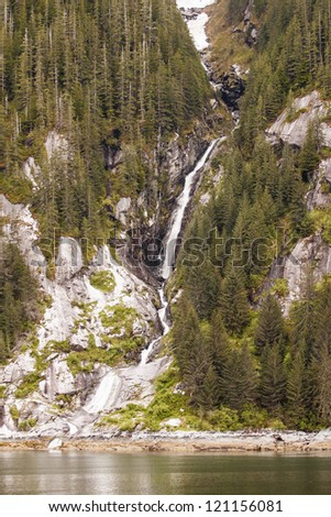 A waterfall cascading through evergreens from melting snow to a calm waterway