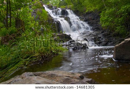A waterfall falling into a pool surrounded by a green spring forest in Northern Minnesota.