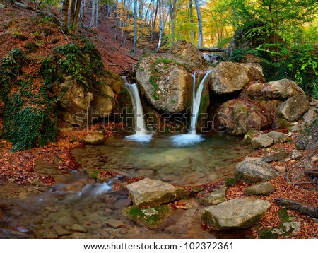 A waterfall in the mountains, around autumn forest with yellow foliage and the blue sky, outdoors