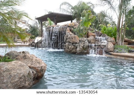 waterfall in to a pool in a luxury backyard with tropical landscaping