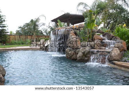 A Waterfall In To A Pool In A Luxury Backyard With Tropical ...