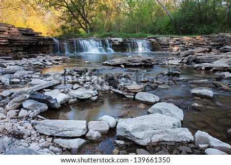 A waterfall supplies a rocky stream with an ample flow of springtime water. Along the stream, pools of water are formed reflecting the soft colors of the morning sunlit trees.