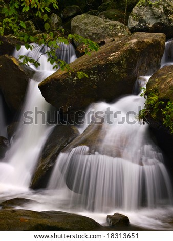A waterfalls near a mountain hiking path. - stock photo